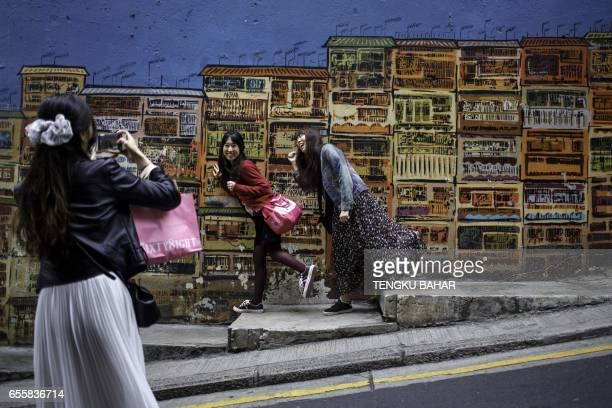 In this photo taken on March 11 Korean tourists pose for photographs in front of street art along Graham Street in Hong Kong's SoHo district From...