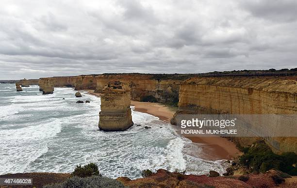 In this photo taken on March 24 waves crash into the base of natural limestone structures known as the Twelve Apostles off the shore of the Port...