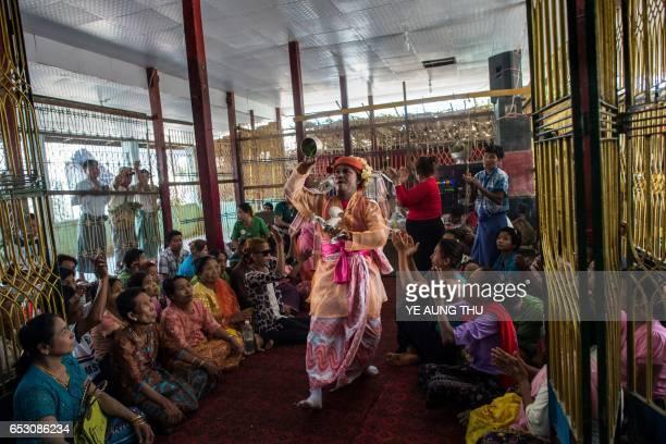 In this photo taken on March 7 a crowd of devotees watch a medium invoke spirits inside a shrine in Shwe Ku Ni village during the Ko Gyi Kyaw Nat...