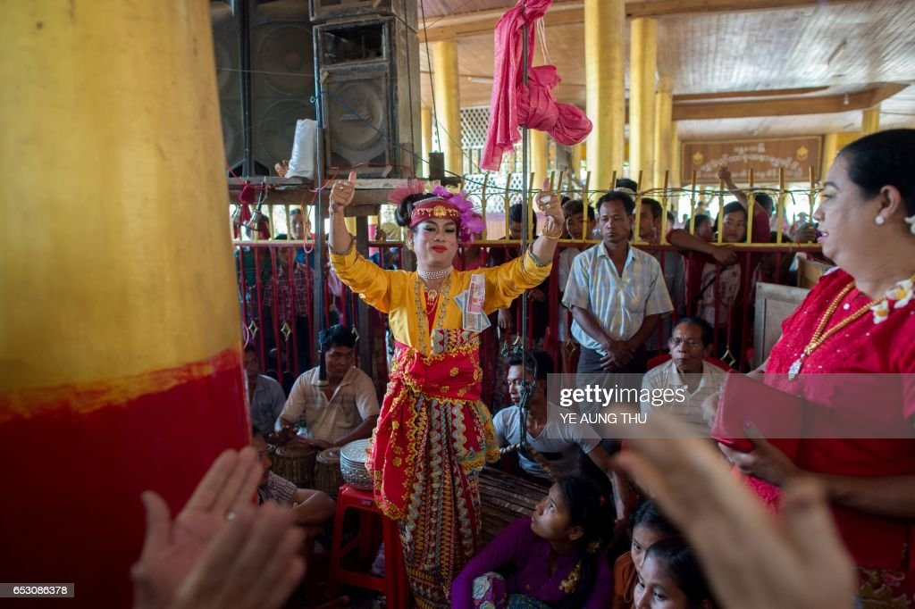 In this photo taken on March 7, 2017, a crowd of devotees watch a medium invoke spirits inside a shrine in Shwe Ku Ni village during the Ko Gyi Kyaw Nat festival. The medium spins around in a frenzy of red and gold while glugging from a bottle of whiskey, part of an age old ritual to honour Myanmar's spirit guardian of drunkards and gamblers. Every year thousands of people pour into a small village southwest of Mandalay for a two-week festival, many packed into boats clutching bags of food and bedding or pulling up on rickety old bullock carts. / AFP PHOTO / Ye Aung THU