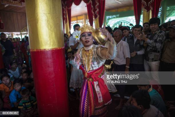 In this photo taken on March 7 a crowd watches a medium dance as he invokes spirits inside a shrine in Shwe Ku Ni village during the Ko Gyi Kyaw Nat...