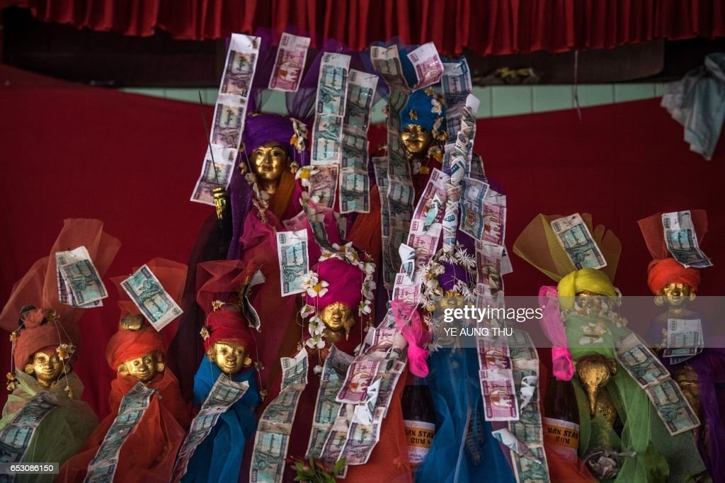 In this photo taken on March 7, 2017, currency notes adorn offerings inside a shrine in Shwe Ku Ni village during the Ko Gyi Kyaw Nat festival. The medium spins around in a frenzy of red and gold while glugging from a bottle of whiskey, part of an age old ritual to honour Myanmar's spirit guardian of drunkards and gamblers. Every year thousands of people pour into a small village southwest of Mandalay for a two-week festival, many packed into boats clutching bags of food and bedding or pulling up on rickety old bullock carts. / AFP PHOTO / Ye Aung THU