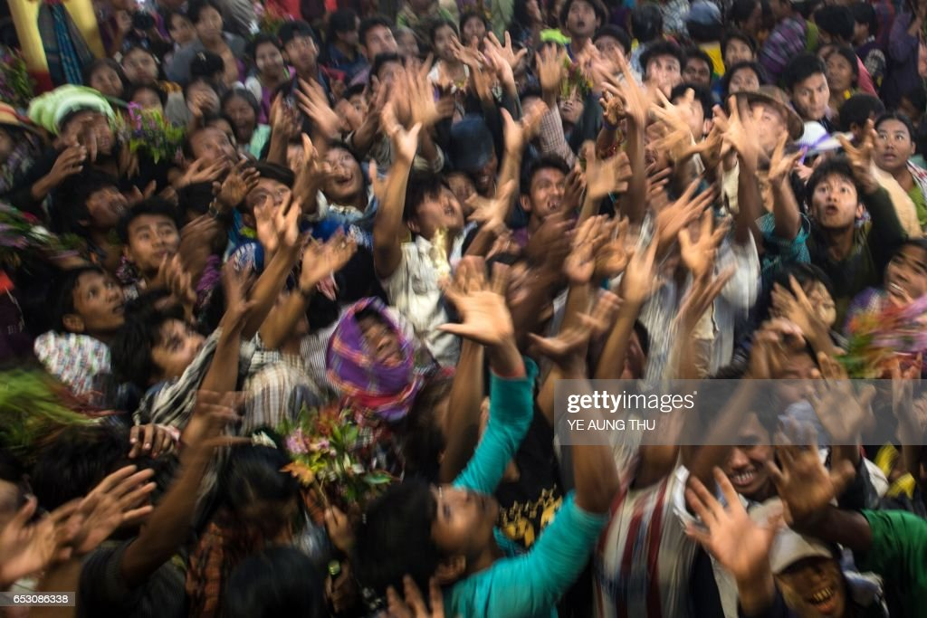 In this photo taken on March 7, 2017, devotees scramble to grab currency notes thrown into the crowd by wealthy participants inside a shrine in Shwe Ku Ni village during the Ko Gyi Kyaw Nat festival. The medium spins around in a frenzy of red and gold while glugging from a bottle of whiskey, part of an age old ritual to honour Myanmar's spirit guardian of drunkards and gamblers. Every year thousands of people pour into a small village southwest of Mandalay for the two-week festival, many packed into boats clutching bags of food and bedding or pulling up on rickety old bullock carts. / AFP PHOTO / Ye Aung THU