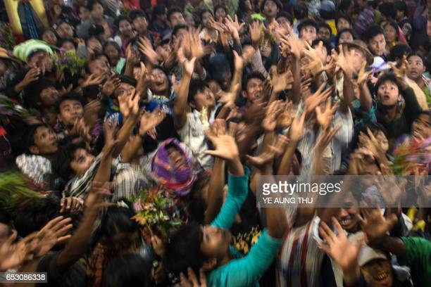 In this photo taken on March 7 devotees scramble to grab currency notes thrown into the crowd by wealthy participants inside a shrine in Shwe Ku Ni...