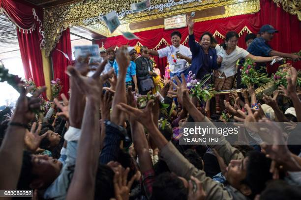 In this photo taken on March 7 devotees scramble to reach currency notes thrown into the crowd by wealthy participants inside a shrine in Shwe Ku Ni...
