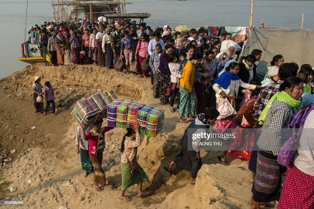 In this photo taken on March 7, 2017, people crowd the banks of the Chindwin river in central Myanmar near Pakhangyi town after disembarking from a ferry as they head to participate in the Ko Gyi Kyaw Nat festival. The medium spins around in a frenzy of red and gold while glugging from a bottle of whiskey, part of an age old ritual to honour Myanmar's spirit guardian of drunkards and gamblers. Every year thousands of people pour into a small village southwest of Mandalay for the two-week festival, many packed into boats clutching bags of food and bedding or pulling up on rickety old bullock carts. / AFP PHOTO / Ye Aung THU