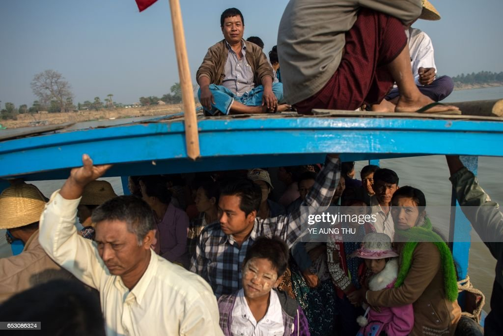 In this photo taken on March 7, 2017, people ride a ferry on the Chindwin river in central Myanmar near Pakhangyi town as they head to participate in the Ko Gyi Kyaw Nat festival. The medium spins around in a frenzy of red and gold while glugging from a bottle of whiskey, part of an age old ritual to honour Myanmar's spirit guardian of drunkards and gamblers. Every year thousands of people pour into a small village southwest of Mandalay for a two-week festival, many packed into boats clutching bags of food and bedding or pulling up on rickety old bullock carts. / AFP PHOTO / Ye Aung THU