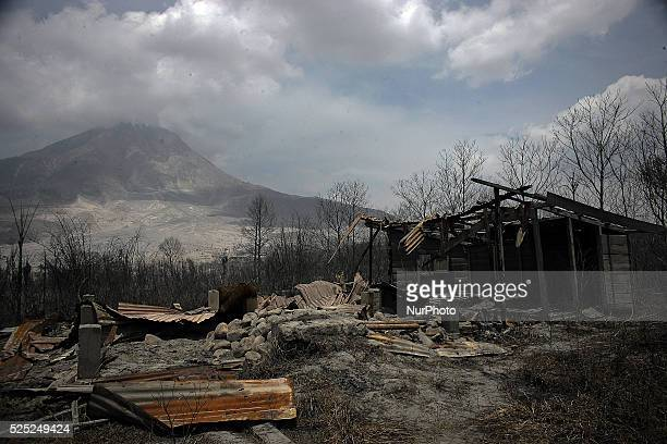 In this photo taken on March 7 the houses were damaged by the eruption of Mount Sinabung eruption lay in ruins recently as seen in the background in...