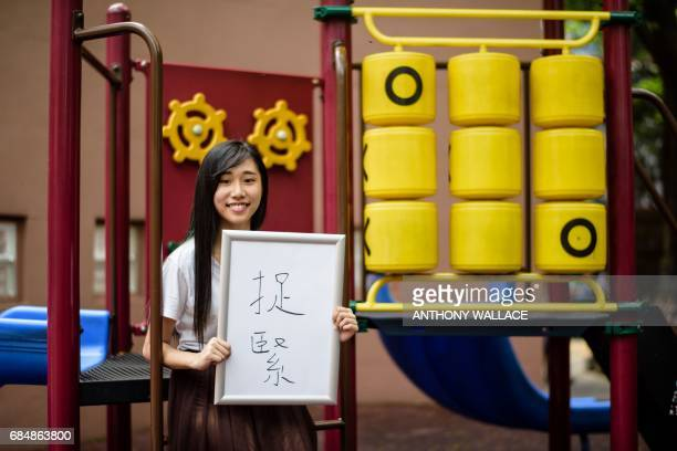 In this photo taken on May 9 20 year old student Chau Hooi who works with prodemocracy party Demosisto holds a board upon which she wrote Chinese...