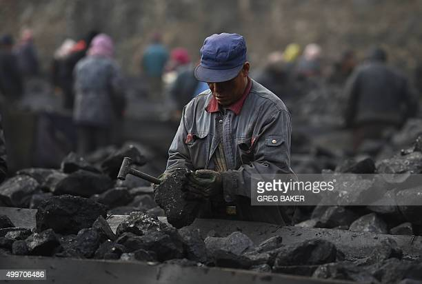 In this photo taken on November 20 a worker sorts coal on a conveyer belt near a coal mine at Datong in China's northern Shanxi province A Chinese...