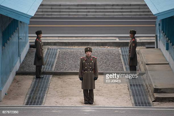 In this photo taken on November 30 Korean People's Army soldiers stand guard at the demarcation line of the joint security area and Demilitarized...
