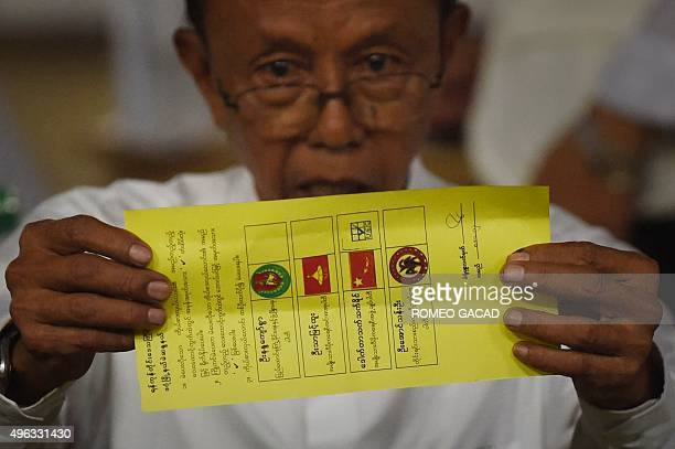 In this photo taken on November 8 a poll official displays a ballot marked for the candidate of Myanmar opposition leader Aung San Suu Kyi's National...