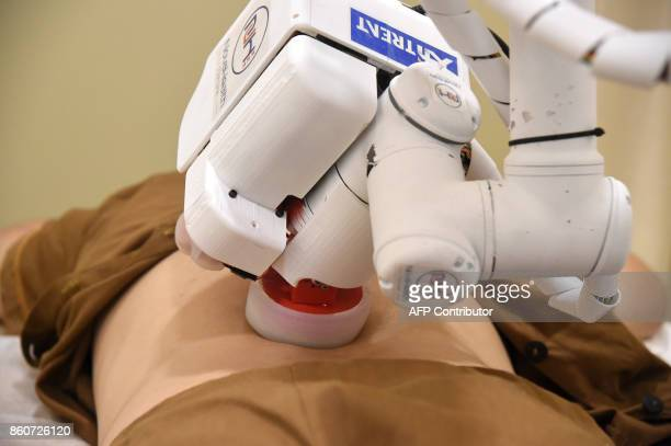 In this photo taken on October 12 a robot masseuse performs a massage on patient Elaine Low at the NovaHealth traditional chinese medicine clinic in...