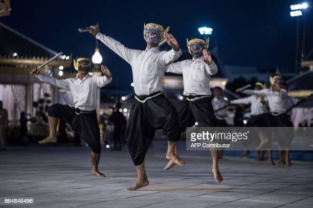 In this photo taken on October 21 2017 masked dancers practice a presentation around the pavilion where Thailand's late king Bhumibol Adulyadej will...