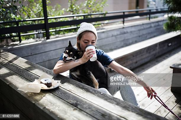 In this photo taken on October 4 coffee drinker Yu Fukuhara holds her Shiba Inu dog Lily as she enjoys her beverage at a coffee shop in Tokyo In a...