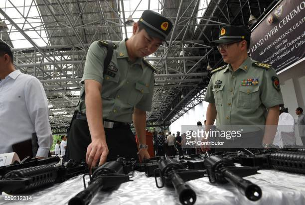 In this photo taken on October 5 China embassy's military attaches of the People's Liberation Army inspect rifles donated by their government to the...