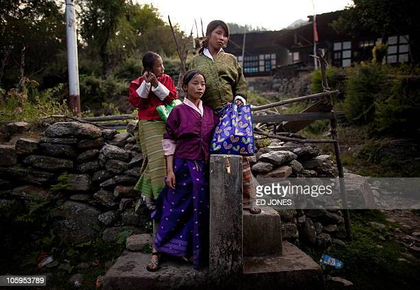In this photo taken on October 6 Bhutanese school girls stand by a water tap on their way home from school in a village near the town of Haa The Haa...