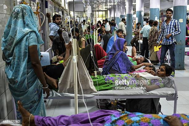 In this photo taken on September 15 2015 18 yearold patient Radha suffering from dengue shares her bed with other patients in a casualty ward of a...