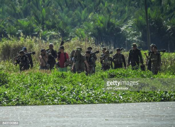 In this photo taken on September 5 2017 shows Moro Islamic Liberation Front rebels from the 118th base command patrolling an area once held by ISIS...