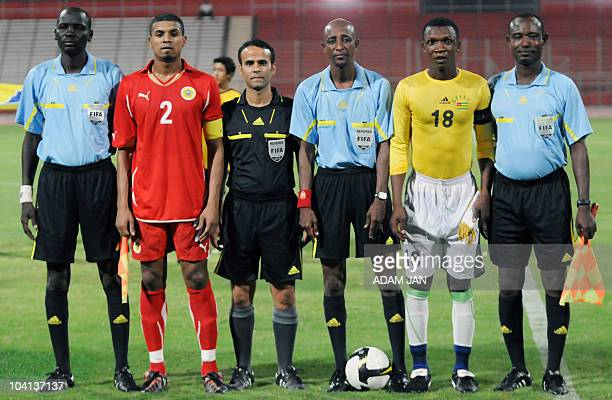 In this photo taken on September 7 Bahraini national football team captain Mohammed Hussain poses for a prematch picture with the alleged captain of...