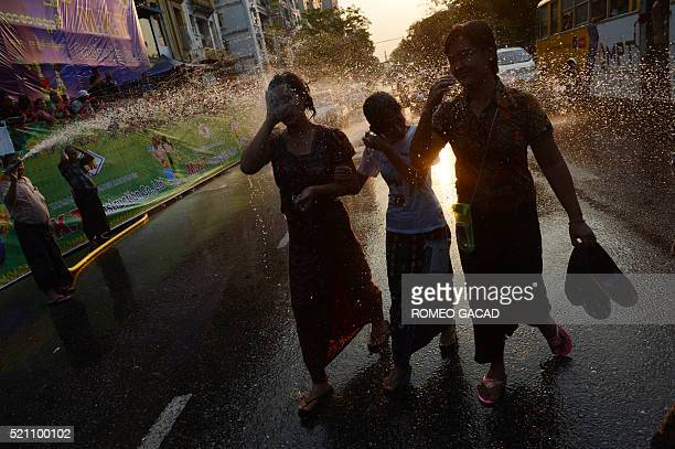 In this photogaph taken on April 13 Myanmar women are doused with water during wet celebrations marking Thingyan a water festival which brings in the...
