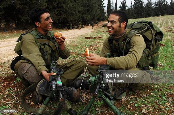 In this photograph distributed by the Israeli Defense Forces infantry soldiers from the elite Egoz unit take a break from operational duty to eat...