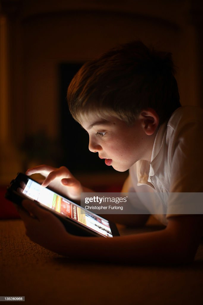 In this photograph illustration a ten-year-old boy uses an Apple Ipad tablet computer on November 29, 2011 in Knutsford, United Kingdom. Tablet computers have become the most wanted Christmas present for children between the ages of 6-11 years. Many parents are having to share their tablet computers with their children as software companies release hundredes of educational and fun applications each month.