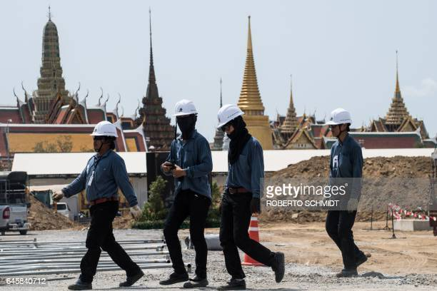 In this photograph taken in Bangkok on February 23 Thai construction workers walk on the grounds of where an enormous largely wooden funeral pyre for...