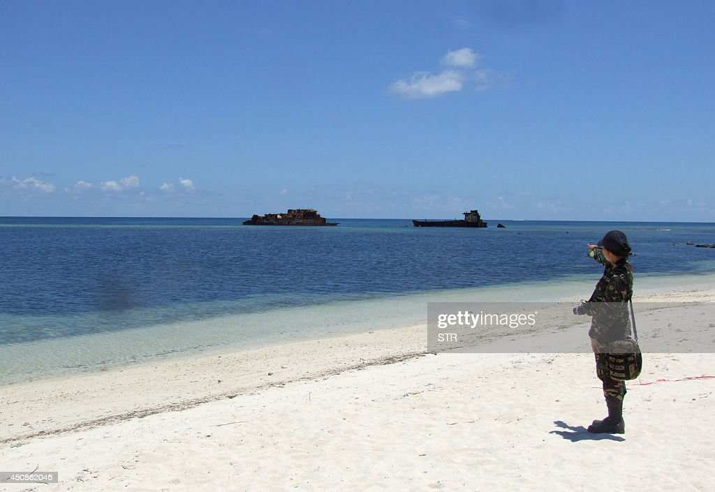 In this photograph taken in June 2014 a military personnel stands on the beach at Thitu island which hosts a small Filipino town as well as an...
