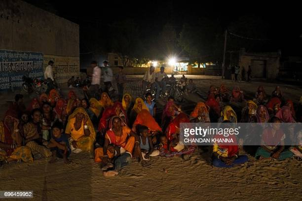 In this photograph taken June 15 Indian people watch a 'Ramleela' folk play in Jaitaran some 80 km north of Jodhpur in the northern state of...