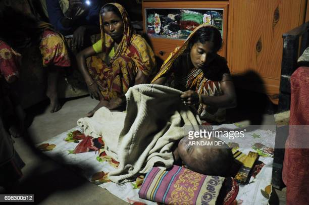 In this photograph taken June 19 2017 Fatema Begum covers the body of her daughter Roona who was suffering from hydrocephalus at their hut in Jirania...