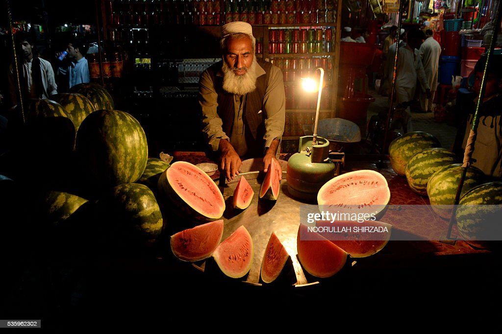 In this photograph taken late May 30, 2016, an Afghan street vendor prepares watermelons for customers at his roadside stall in Jalalabad. / AFP / NOORULLAH