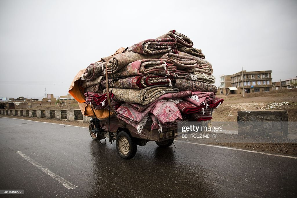 In this photograph taken on April 1, 2014, a motorcycle laden with Afghan and Iranian carpets transports them to the shops in the northwestern city of Herat. Carpets are Afghanistan's best-known export, woven mostly by women and children in the north of the country, a trade which once employed, directly or indirectly, six million people, or a fifth of the country's population, but that figure has dropped sharply.