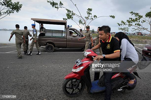 In this photograph taken on April 11 an Acehnese man and woman drive off on a motorcycle after being spotted by sharia police dating on riverside...