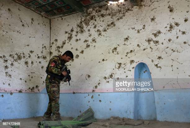 In this photograph taken on April 11 an Afghan security force personnel patrols inside a mosque during an ongoing an operation against Islamic State...