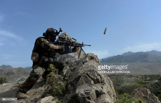 TOPSHOT In this photograph taken on April 11 an Afghan security force personnel fires during an ongoing an operation against Islamic State militants...