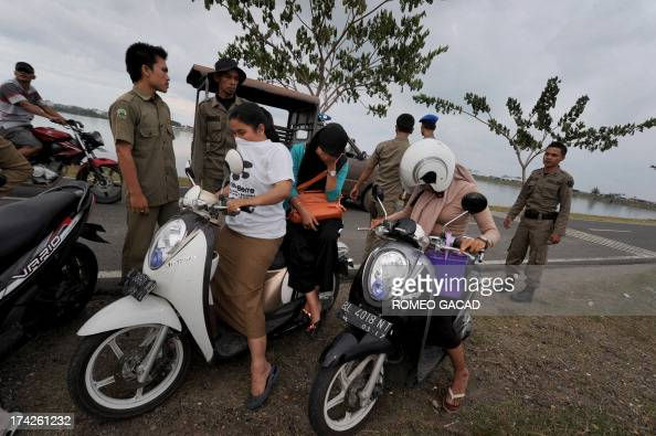 In this photograph taken on April 11 sharia police accost a woman on a motorcycle for not wearing a headscarf during a patrol of Lhokseumawe city in...