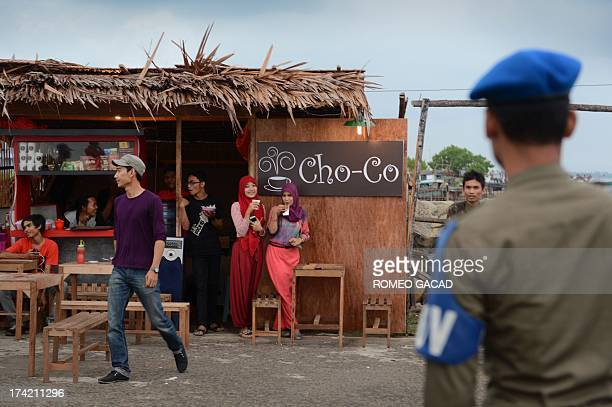 In this photograph taken on April 11 sharia police observe women customers on a road side food stall during a patrol of Lhokseumawe city in Aceh the...