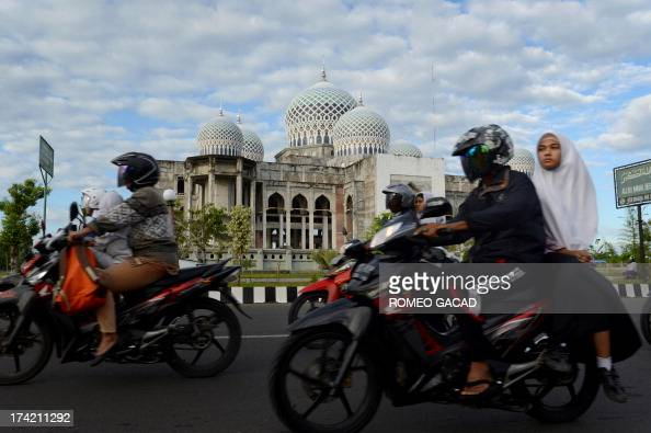 In this photograph taken on April 12 an Acehnese woman rides on a motorcycle in Lhokseumawe city in Aceh the only province to implement Islamic...
