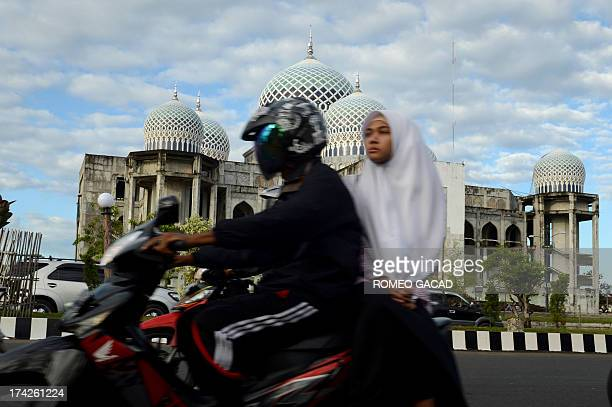 In this photograph taken on April 12 an Acehnese woman rides on the back of a motorcycle in Lhokseumawe city in Aceh the only province to implement...