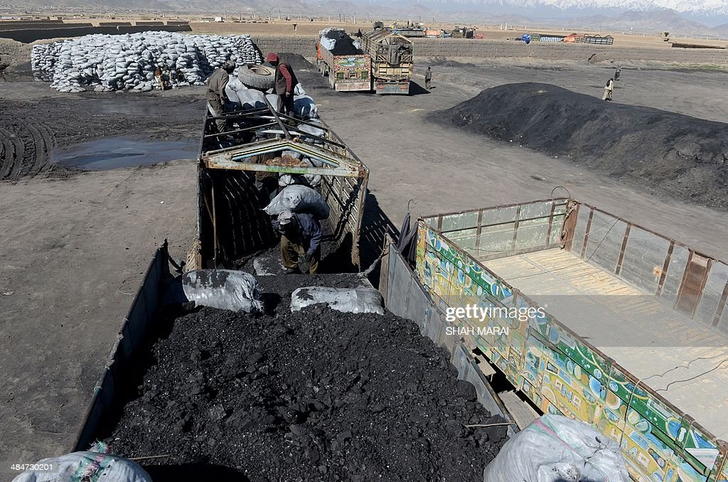 In this photograph taken on April 13, 2014, an Afghan day labourer loads coal onto a truck on the outskirts of Kabul. Coal labourers work an average of eight hours a day filling trucks with coal, each earning around seven USD on an average working day. Most of them come from the northern provinces, leaving their families behind in search of fortune in the capital. To cut the high cost of living the labourers live in rooms housing 18-20 people, on a diet that usually consists of tea and bread. AFP PHOTO/SHAH Marai