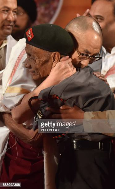 In this photograph taken on April 2 Tibetan spiritual leader the Dalai Lama hugs retired Assam Rifles personnel Naren Chandra Das the lone known...