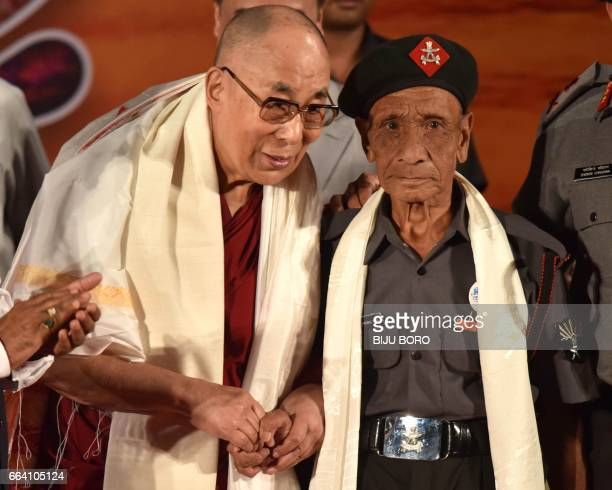 In this photograph taken on April 2 Tibetan spiritual leader the Dalai Lama shakes hands with retired Assam Rifles personnel Naren Chandra Das the...