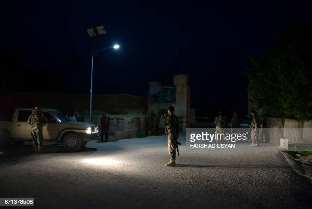In this photograph taken on April 21 Afghan security personnel stand guard near the site of attack on an army compound in Dihdadi District of Balkh...