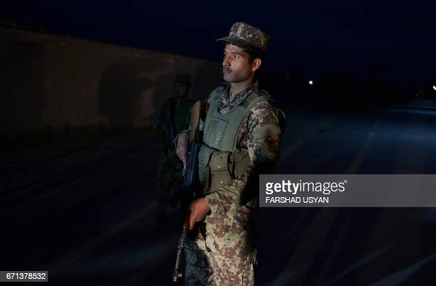 In this photograph taken on April 21 an Afghan security official stands alert near the site of attack on an army compound in Dihdadi District of...