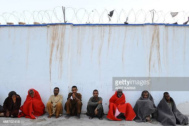 In this photograph taken on April 23 Afghan patients rest behind a wall at the only mental health rehabilitation centre in the city of Herat...