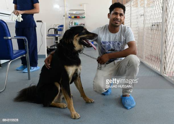 In this photograph taken on April 24 Indian dog owner Sunil Kumar and his dog Kuku pose for a photogrpah after Kuku underwent a blood test at the...