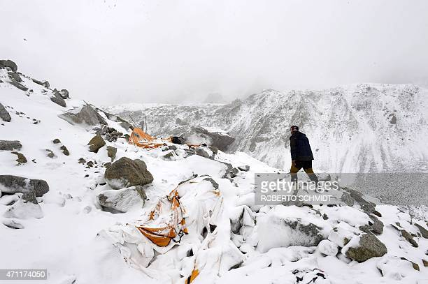 In this photograph taken on April 25 expedition guide Pasang Sherpa runs towards flattened tents in search of survivors after an avalanche that...