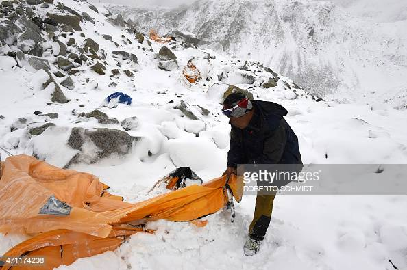 In this photograph taken on April 25 expedition guide Pasang Sherpa searches through flattened tents in search of survivors after an avalanche that...