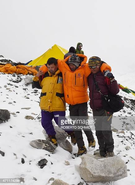 In this photograph taken on April 25 rescuers assist an injured person after an earthquake triggered by an avalanche flattened parts of Everest Base...